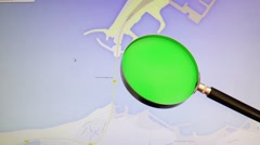 A green painted magnifying glass in front of a monitor showing a google map Stock Footage