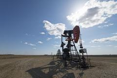 A pump jack in open ground at an oil extraction site. Stock Photos