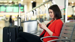 Pretty woman with smartphone sitting at train stationHD Stock Footage