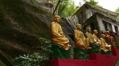 Mystical golden Buddhas statues on shadow pathway, close up view Stock Footage