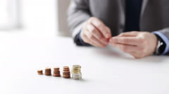 close up of businessman putting coins into columns - stock footage