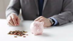 Close up of man putting coins into piggy bank Stock Footage