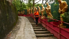 Man carrying baby and woman climb up to monastery, Golden Buddhas aside Stock Footage