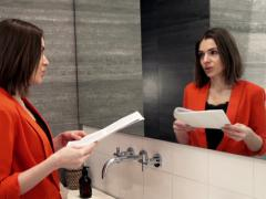 Young businesswoman trying her speech in front of the mirror in bathroom NTSC Stock Footage