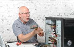 An angry man destroy his computer Stock Photos