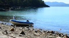 Lady and Dinghy in Empty Rocky Island Bay - stock footage