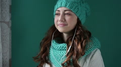 Beautiful woman in a knitted hat listening to music Stock Footage