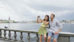 Europe travel romantic couple tourists Stockholm taking selfie photo having fun Stock Footage