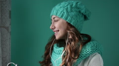 Beautiful woman in a knitted hat listening to music - stock footage