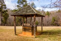 old historic water well in the forest - stock photo
