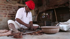 Indian man forming pliable material with a sharp tool in workshop in Jodhpur. Stock Footage