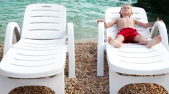 Little boy tans on the sea coastline in white deck chair Stock Footage