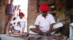 Indian men peeling pliable material on the floor of a workshop in Jodhpur. Stock Footage
