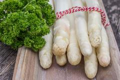 Bundle of white asparagus  with parsley - stock photo