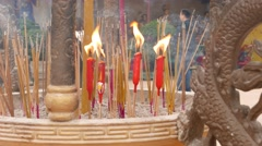 Close up incense sticks and burning candles, daytime, Buddhist temple Stock Footage
