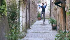 Enthusiast young man exulting while running in a little street with stairs Stock Footage