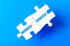 Connected puzzle pieces with words BUSINESS and STRATEGY  Stock Illustration
