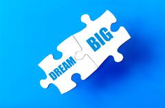 Connected puzzle pieces with text DREAM BIG  - stock illustration