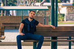 Handsome smiling and casual young man sitting on bench Stock Photos