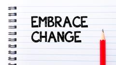 Embrace Change Text written on notebook page, red pencil on the right. Motiva Stock Photos