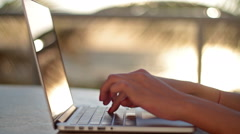 Girl typing on a laptop at sunrise - stock footage