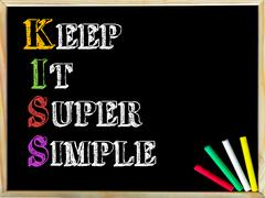 Acronym KISS as KEEP IT SUPER SIMPLE. Written note on wooden frame blackboard Stock Photos