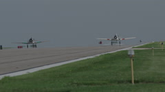 Two American T-6 Texan warbirds taxiing on runway of Wittman Regional Airport - stock footage