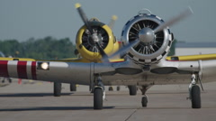 Two North American T-6 Texan warbirds on runway of Wittman Regional Airport - stock footage