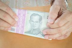 Man hand counting Thai baht banknote Stock Photos
