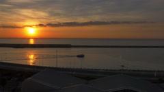 Yellow orange sun ocean small boat passing jetty morning traffic-HD P 0031 Stock Footage
