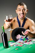 Stock Photo of Man drinking and playing in casino on dark