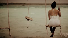 Woman on swing over lake Stock Footage
