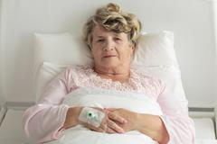 Elder woman with IV drip - stock photo