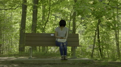 Woman texting while sitting on park bench. 4K UHD. Stock Footage