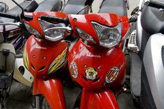2 red honda mopeds, Hanoi street, Vietnam Stock Photos