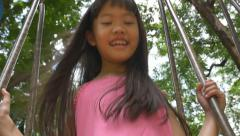 Little Asian girl playing on swing set in the playground, slow motion Stock Footage