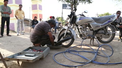 Mechanic repairing motorcycle tire at street while Indian men sit aside. Stock Footage