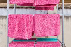 pink towel on clothesline in sunny day - stock photo