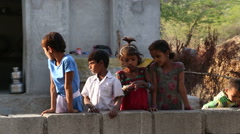 Group of children standing by the wall in front of a house entrance. Stock Footage
