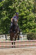 Front view of blonde horsewoman jumping - stock photo
