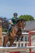 Young horsewoman is jumping. Vertically. - stock photo