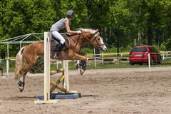 Side view of horsewoman jumping - stock photo