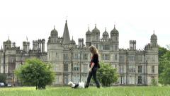 Pretty young woman walking dog, Burghley House, England. Stock Footage