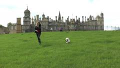 Pretty young woman running with dog, Burghley House, England. Stock Footage