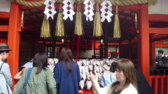 Pan right footage of people and tourists walk Fushimi Inari Shrine in Kyoto. Stock Footage