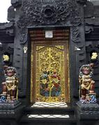 Ornate gilded decorative Hindu temple door, Dempasar, Bali, Indonesia - stock photo