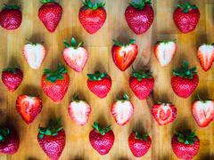 Arranged pattern of strawberries on a wooden board Stock Photos
