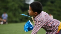 Slow motion:Happy chinese boy playing toy plane in park Stock Footage