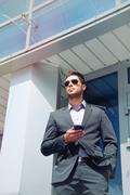 attractive young businessman with phone device in hands on office building ba - stock photo