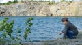child teen boy throwing stones into the water of the lake 002  Footage